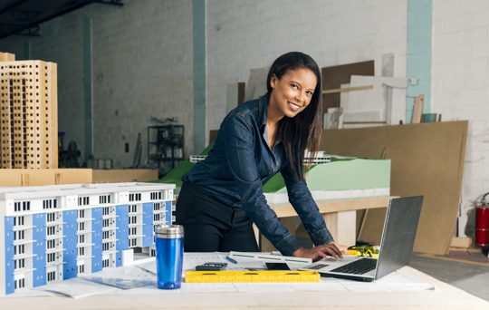 happy-african-american-lady-with-laptop-model-building-table_23-2148039872